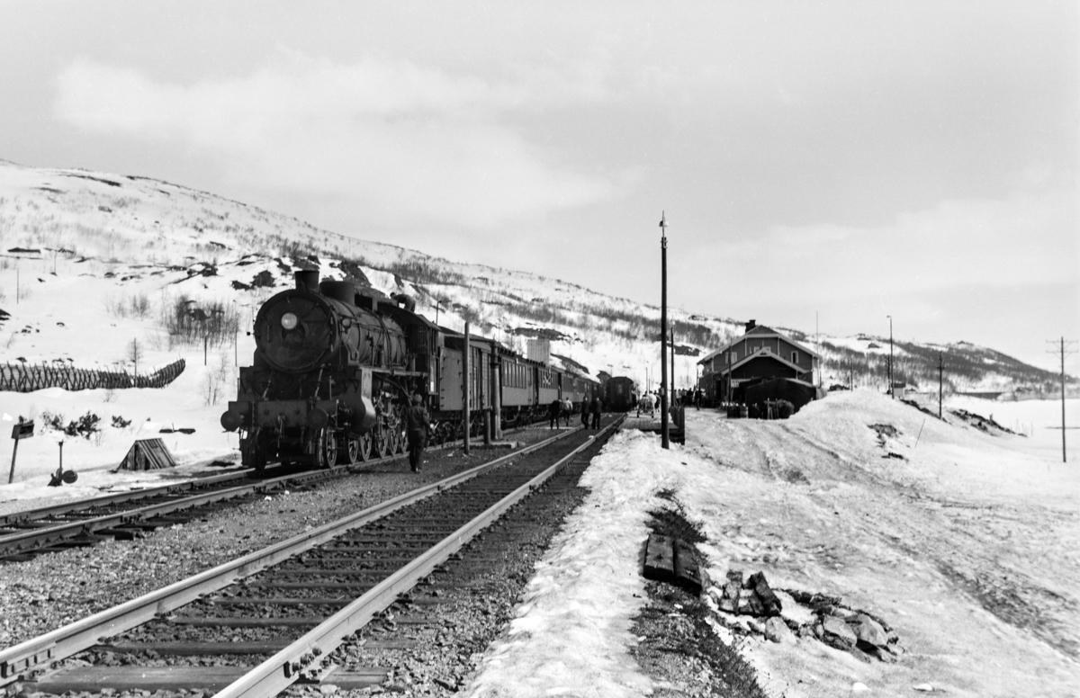 Påsketog retning Bergen, tog 7683, i spor 2 på Haugastøl stasjon. Toget trekkes av damplokomotiv type 31b nr. 428. Kryssende tog skimtes i spor 1.