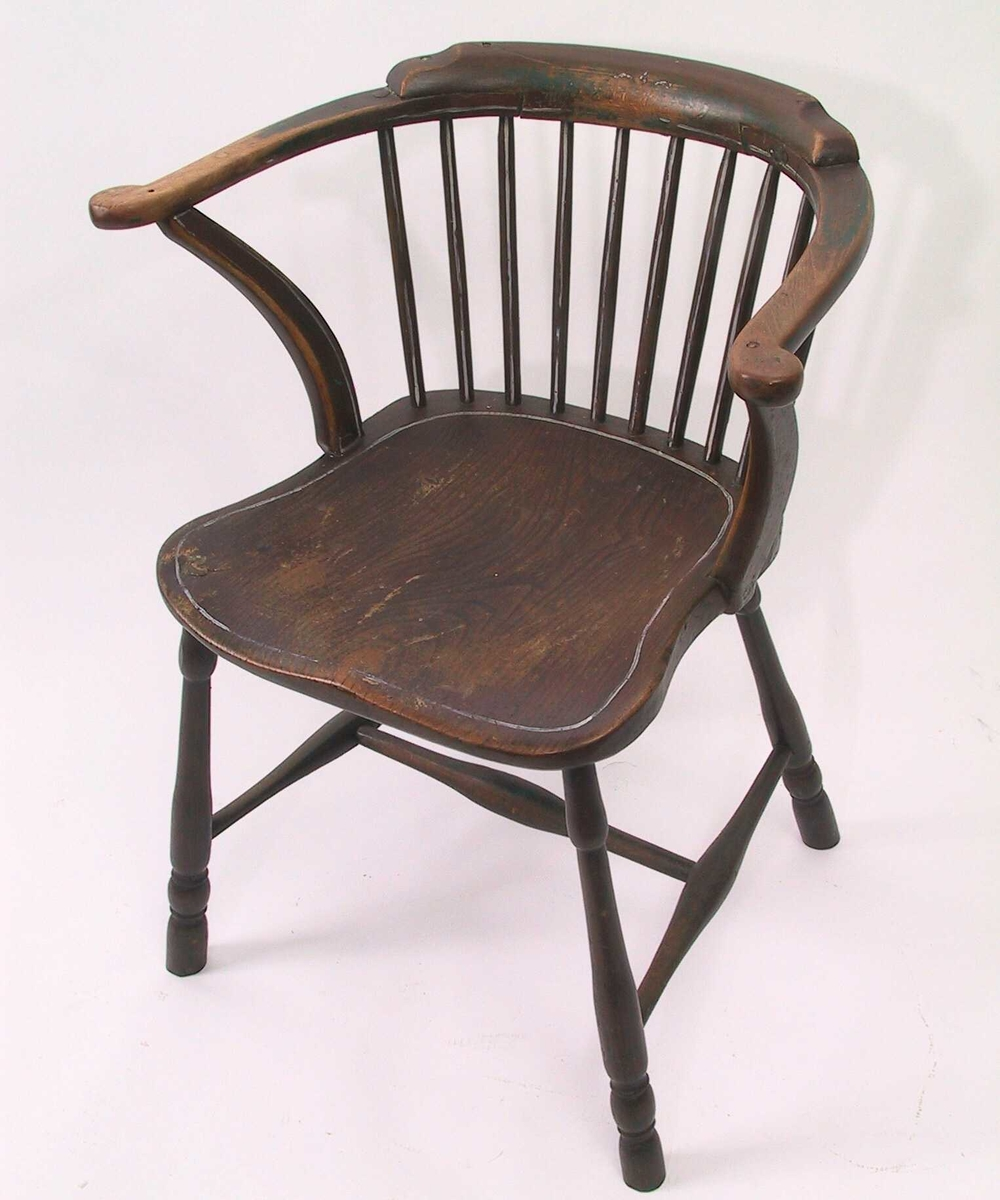 Høy pinnestol med lener. smalt langt sete, figurformet.  Dreide ben, H kryss med slanke spiler, som er tykkere pm. To rader med spiler, den nedre rad med armlene som fortsetter horisontalt spiler, med et glatt toppstykke. Nedre rad har 14 spiler plus en på hver side ytterst mer dekorativt utformet. Langs kan en hvit stripe, nå delvis eller helt slitt av. Tilstand: malingen helt avslitt på lenene, i setet, som har pute, bare i forkant. Under den brune maling ligger grønn ma farge. V. spil i øvre rad i ryggen er løs, spil nr 2 gra h. er reparert før stolen ble brunmalt. Ad stoltypen, se   b) Pute. L. ea. 53. B. ca. 40. Oval pute med den ene langside bare svakt buet, tung og ganske tykk, trukket med sort stoff, monstret med bladranker. D annen med en skjøt pm.