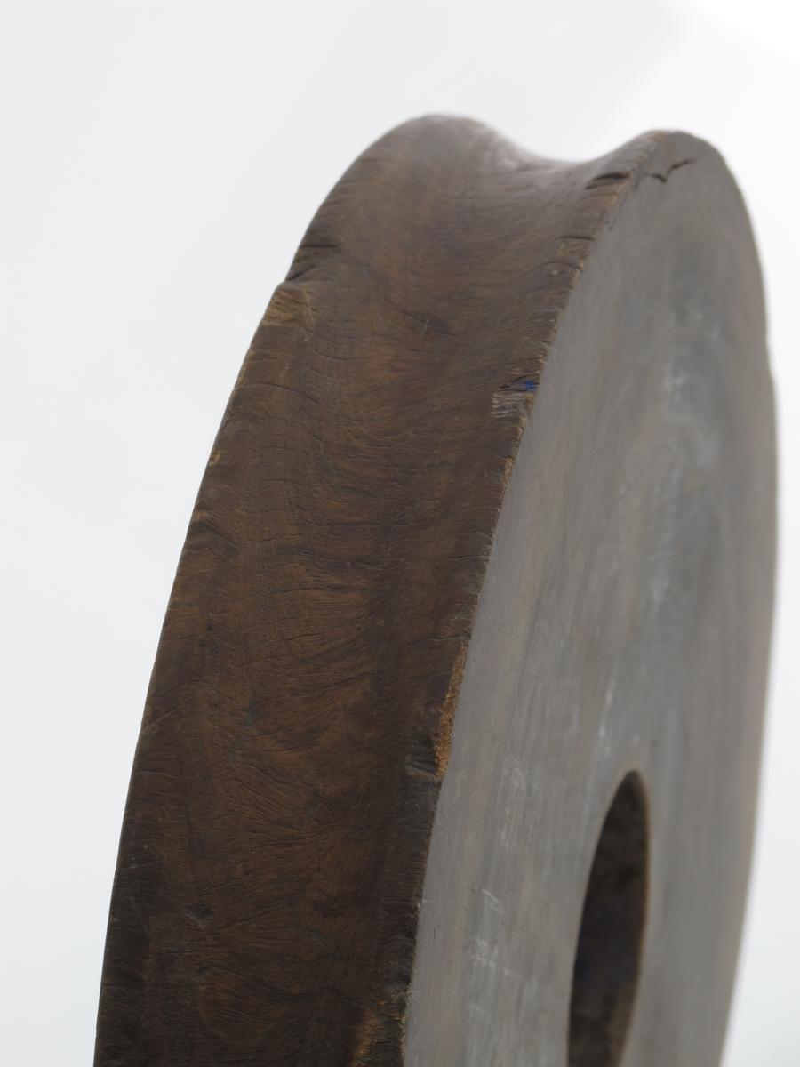Blokkskive av pukkenholt. Dreid, rund skive med hull midt i. Ytre kant konkav. Tilstand juli 1977: Merker etter slitasje, men god.