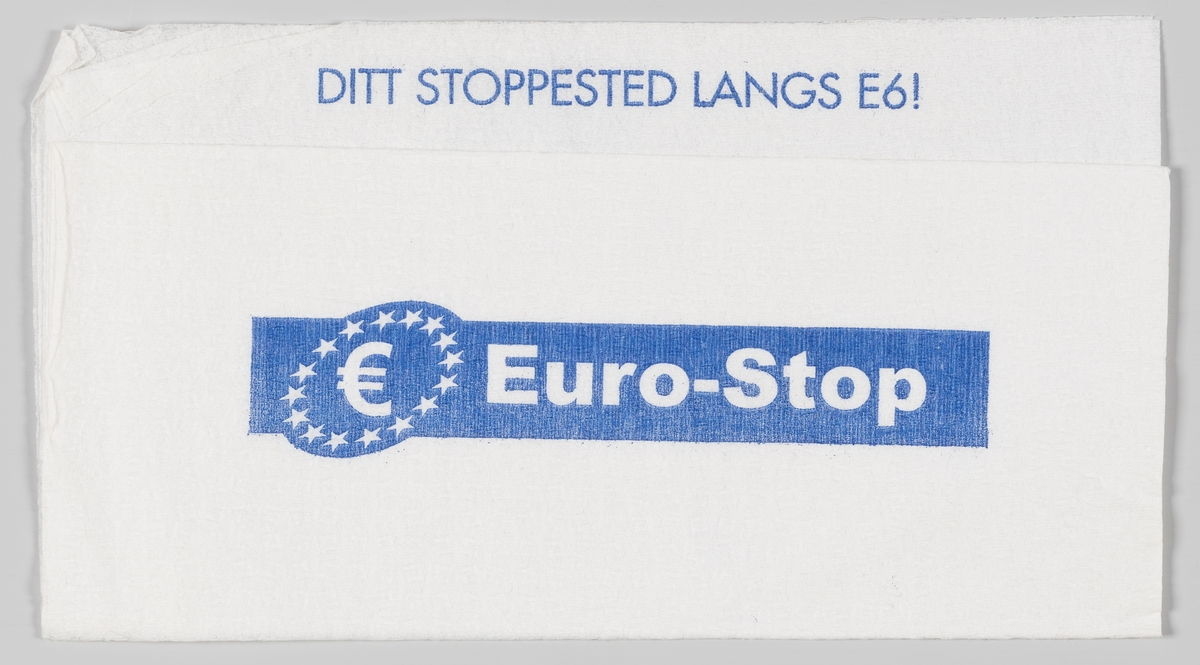 En rundt logo med et E og stjerner langs kanten, et veikart og en reklametekst for Euro-Stop.  Eurostop er en kjede av bemannede rasteplasser. De omgivende parkeringsplasser er tilpasset tung trafikk.