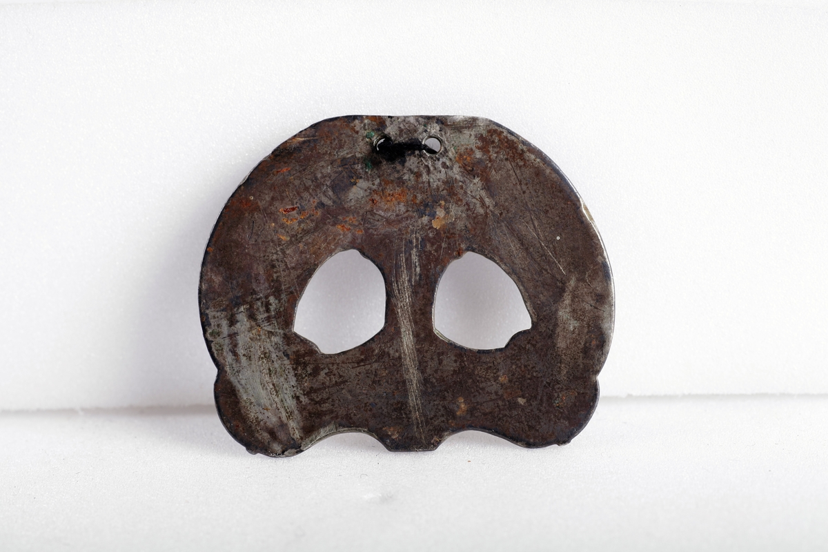 Sølvbeslag og en liten del av dens festeinnretning, forgylt med nielloinnlegg, som type R. 200 d fra eldre jernalder. Utsmykning til sverdslire. Funnet i en gravhaug på gården Mellom-Kvem.