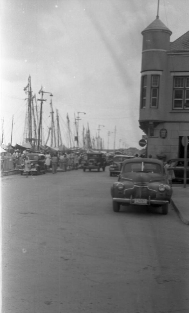 Gateparti. Kaien med seilbåter til venstre og bebyggelse til høyre. Biler og personer i gaten. Suderøy på vei til fangstfeltet.