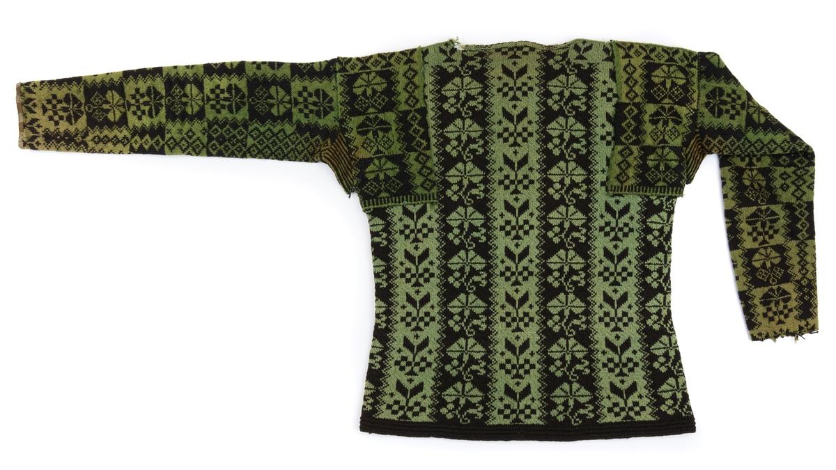 Manströja, mönsterstickad på rundstickor, av hårdtvinnat ullgarn i grönt och svart. Mönster i ränder med nejlikor och bladornament. Ärmspjäll smalrandiga i svart och grönt. Ena ärmen är kantad med brunrandigt linne, den andra är trasig nertill.