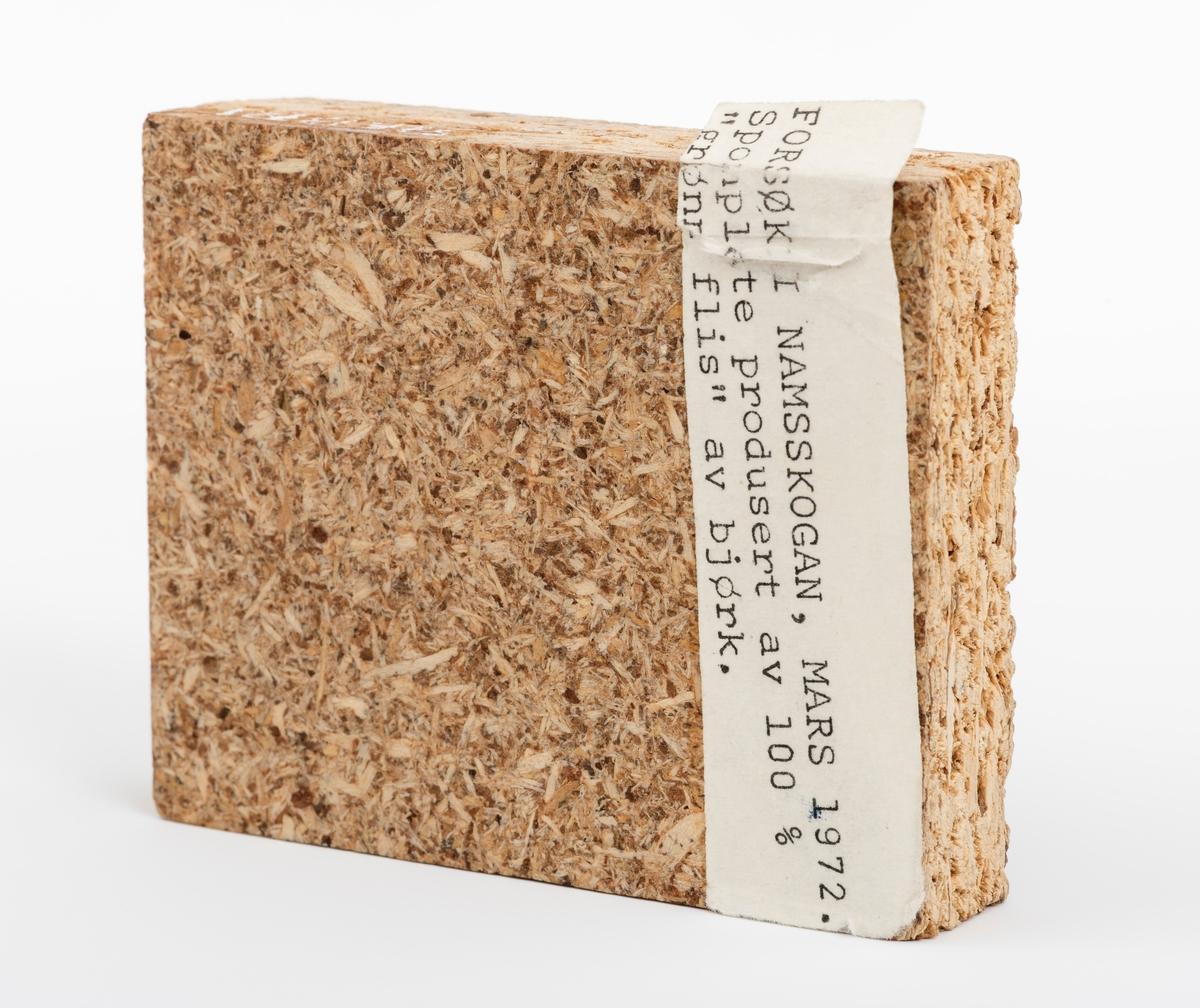 """En rektangulær sponplate, vareprøve på 8,8 cm x 7 cm x 1,8 cm. Plata har glatt fram- og bakside.  På vareprøvas ene side er det påklistret en lapp med denne teksten: """"Forsøk i Namskogan, mars 1972. Sponplate produsert av 100 % """"grønn flis"""" av bjørk"""""""