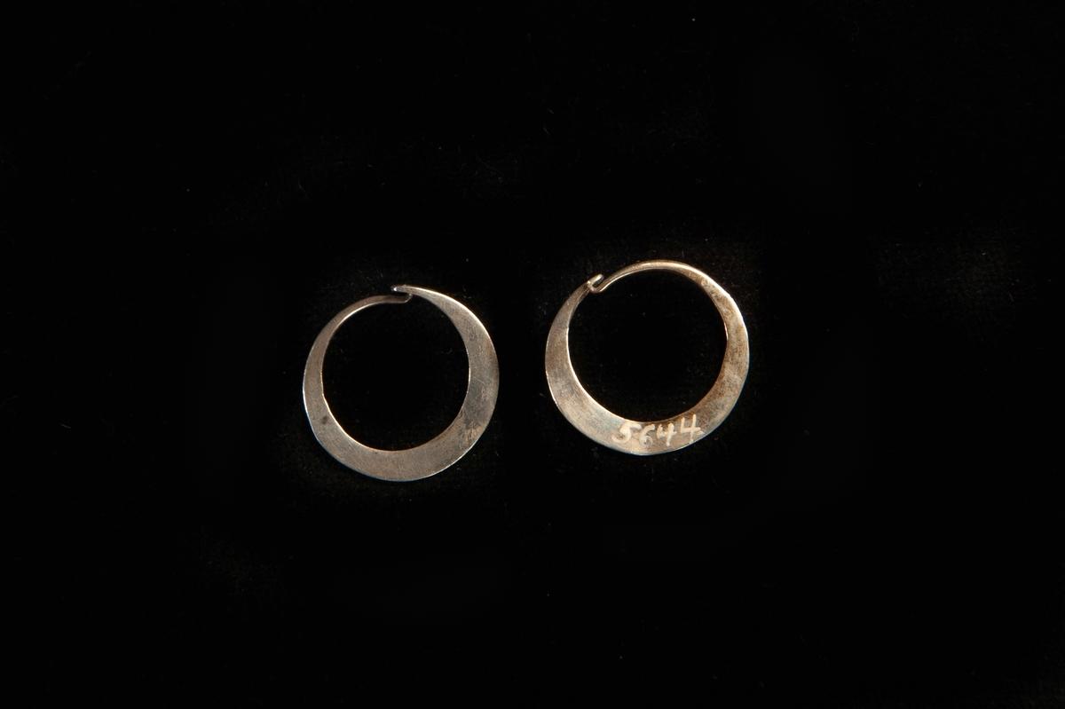 En rund örring av silver. Platt, enkel modell. Hör ihop med JM.5644:1
