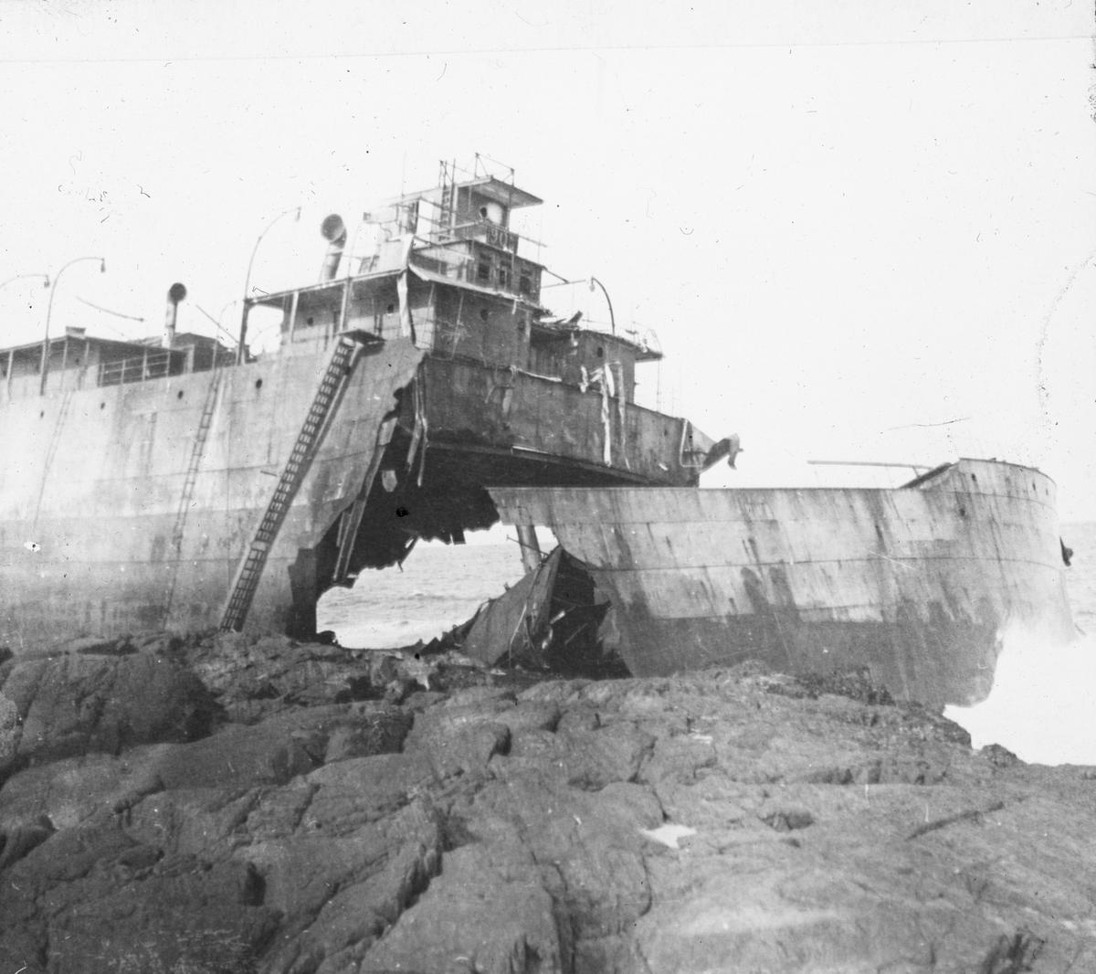 Forskipet på et fartøy satt på land, hele baugen er av, deler av skipssiden er også satt på land.