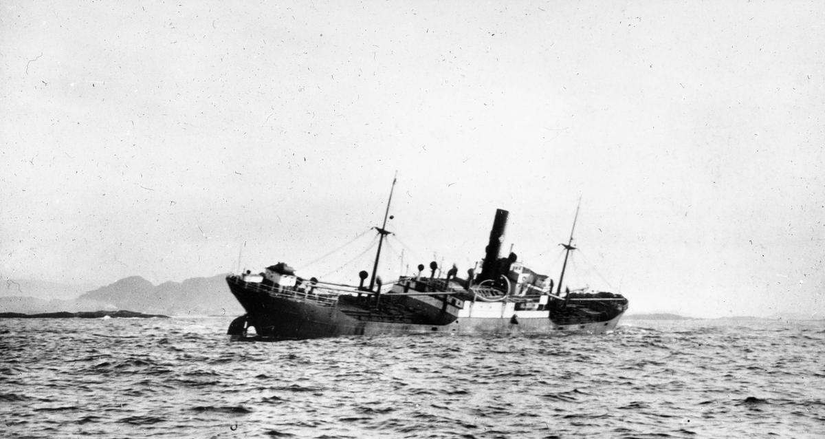 Dampskip med slagside på åpent hav.