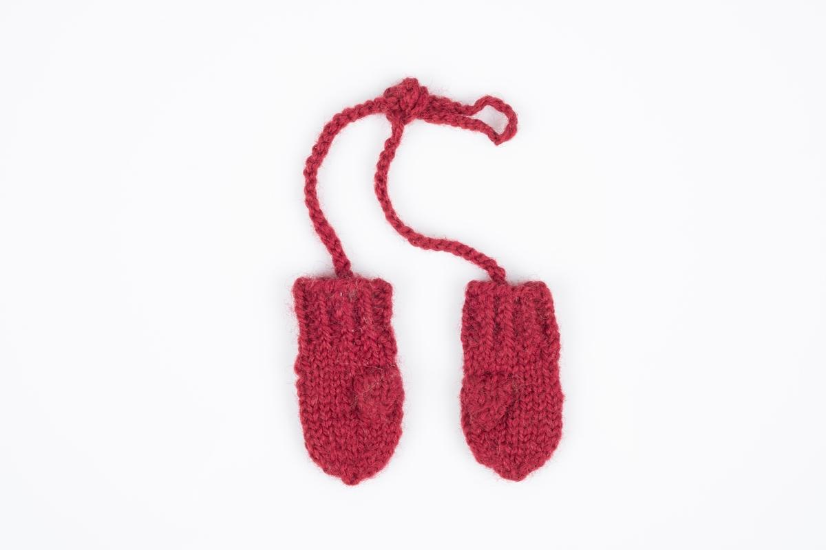 Miniatyrvotter strikket med rødt garn. På håndbaken er det broderier. Vottene er bundet sammen.