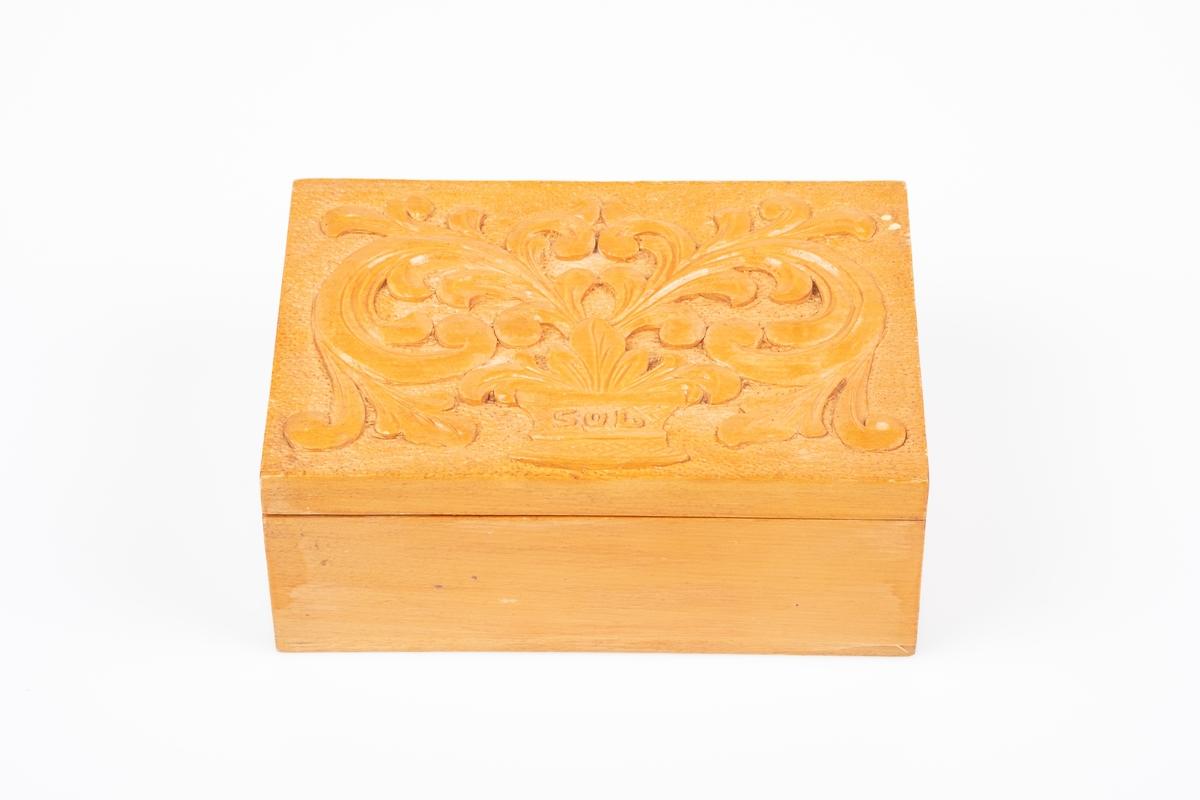 Et treskrin med lokk. Lokket har utskåret akantusmønster. På innsiden av lokker er det skrevet en hilsen.