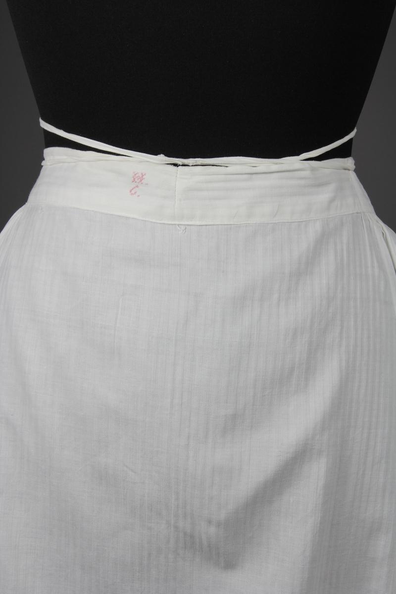 Underkjol av vitt bomullstyg. Tyget är vävt randigt i smala ränder med kypert och tuskaftsbindning. Kjolen är utställd, har ett sprund mitt bak och sydda kanaler upptill bak. Sprundet stängs med bomullsband som är trädda genom kanalerna och gör att storleken kan jysteras i midjan. Mitt fram är kjolen slät i ett 27 cm långt parti. Sedan är kjolen rynkad mot linningen hela vägen bak till sprundet. Kjolen är skuren i sex våder. Lågot längre bak än fram. I nederkanten är det påsytt en list längs hela kjolen och listen är upplagds i tre veck runt om. Längs kjolens nedre fåll är ett sicksackband sytt mot insidan och bildar en uddkant längst ut. Plagget är till större delen sytt på symaskin med raksöm. Lagningar och stoppningar gjorda för hand.