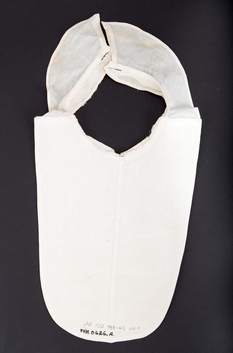 Ovalt skjortebryst (nr a) Stivet front. Linning rundt halsen med knappehull midt foran og knappehull i hver ende for lukking i nakken. Sammensydd midt foran. To stivede mansjetter (b.1-2) med knappehull i begge ender til lukking