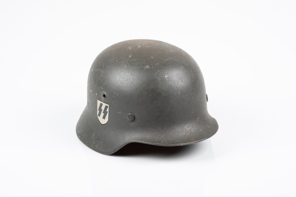 """Tysk soldathjelm i metall med """"SS"""" logo. Hjelmen har to sirkelrunde hull på hver side, som er symmetrisk plassert i forhold til hverandre. På innsiden er det festet en innerhjelm av lær med snor som brukes til å tilpasse hjelmen etter hodets størrelse. Hjelmen har lærrem med metallspenne. Hjelmen er malt brun-grønn."""