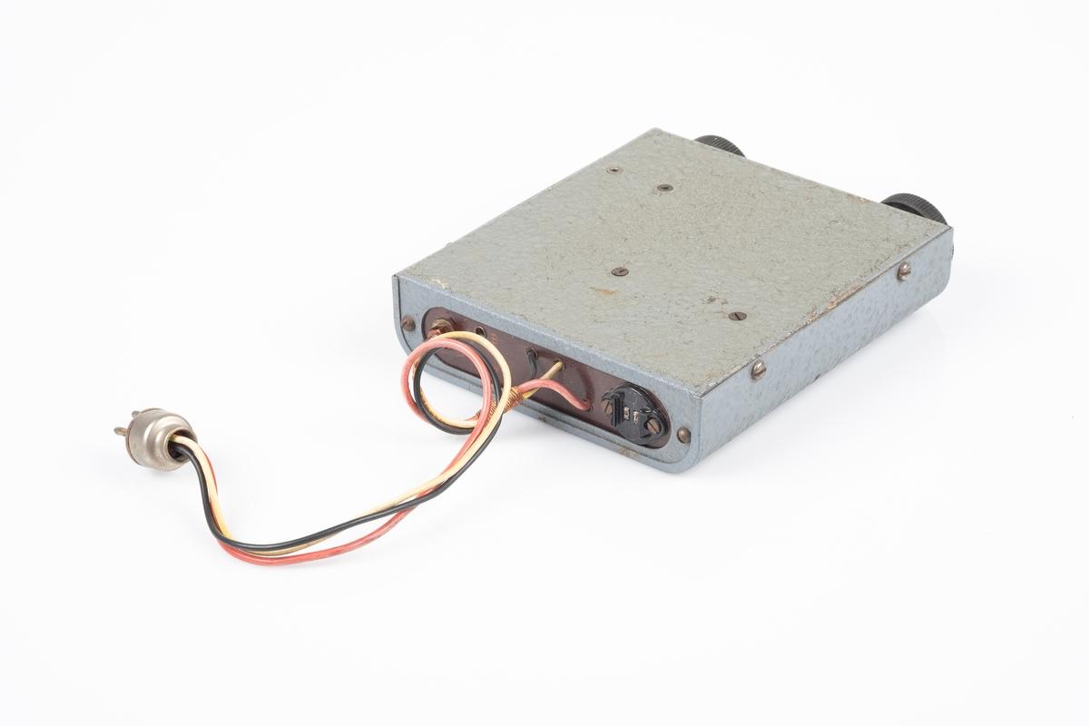 En kortbølgeradio med ytterplater er av metall som er lakkert i grått. Radioen har to svarte vriknapper. Det er et lite vindue ved den ene vriknappen som viser frekvensen. På baksiden er det ledning som kobles til batteriet. Det er to hull til plugger og en kontakt for øreproppene. Det er påfestet en plate med instrukser på på oversiden. Mellom vriknappene er det påfestet en liten plate med modellnummer.