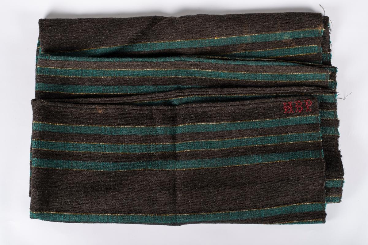Mørk brunt tekstil med gule og grønne striper. Bomullsrenning og innslag av ulltråd. Tekstilet har en grov overflate, og det er lagt inn nauthår som forsterkning. Hestedekkenet er opprinnelig i to deler, men er sydd sammen på midten. Det er brodert inn HBP med rød tråd. Dette er sannsynligvis initialene til Hans Bernhard Præsterud.
