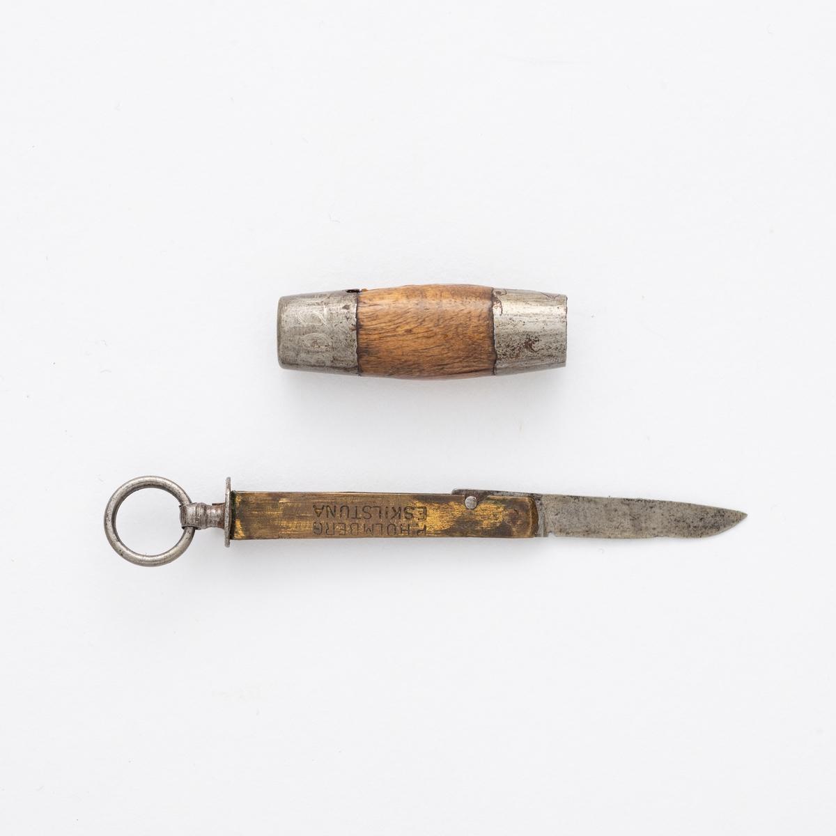 Liten sammenleggbar kniv i stål og messing med oval slire i tre og metall. Metallring til å trekke kniven ut av sliren.