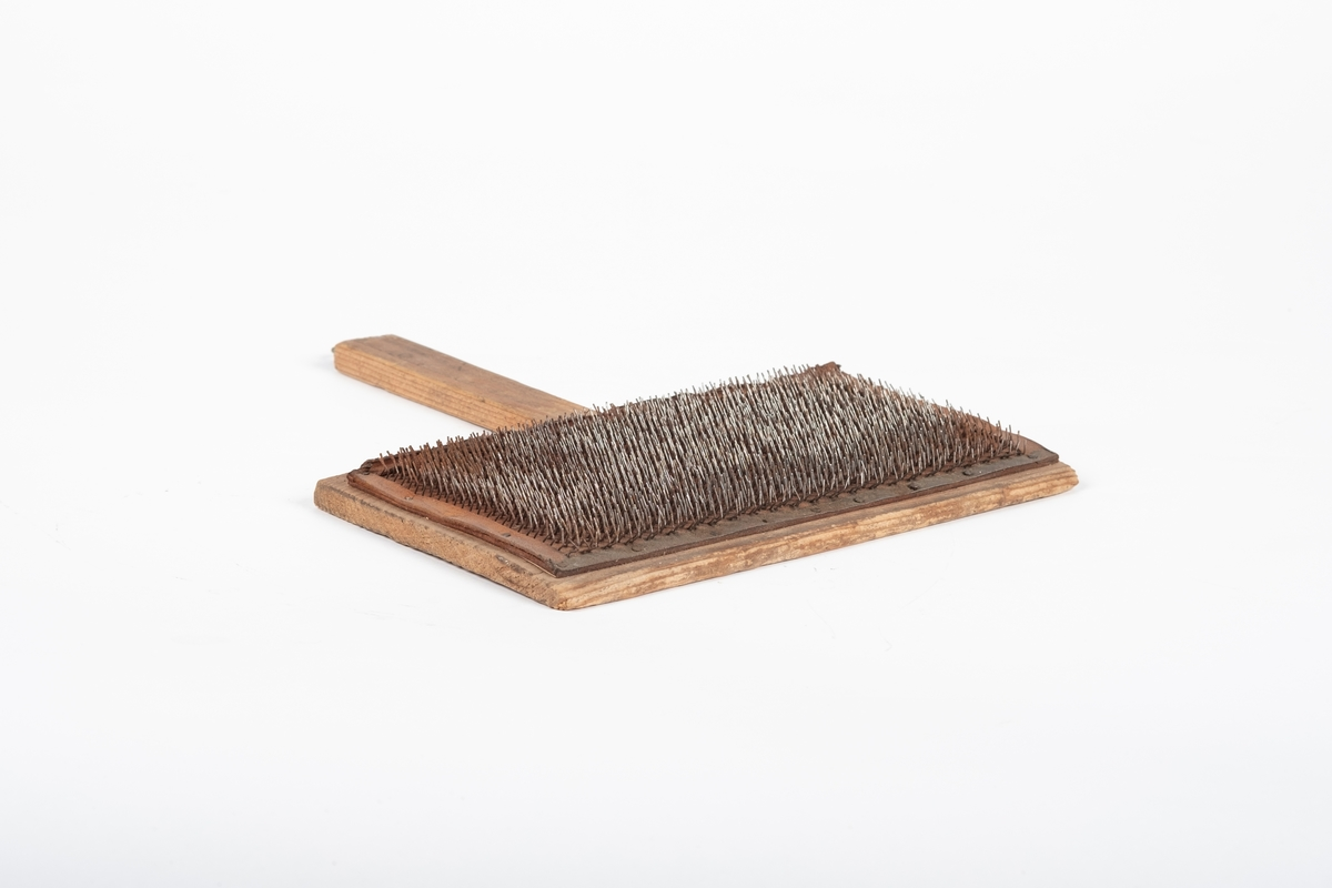Karden består av et trestykke med innfelt håndtak, og med lærstykke fullt av små metallstenger som er festet til trestykket. På håndtaket er det skrudd fast en krok.
