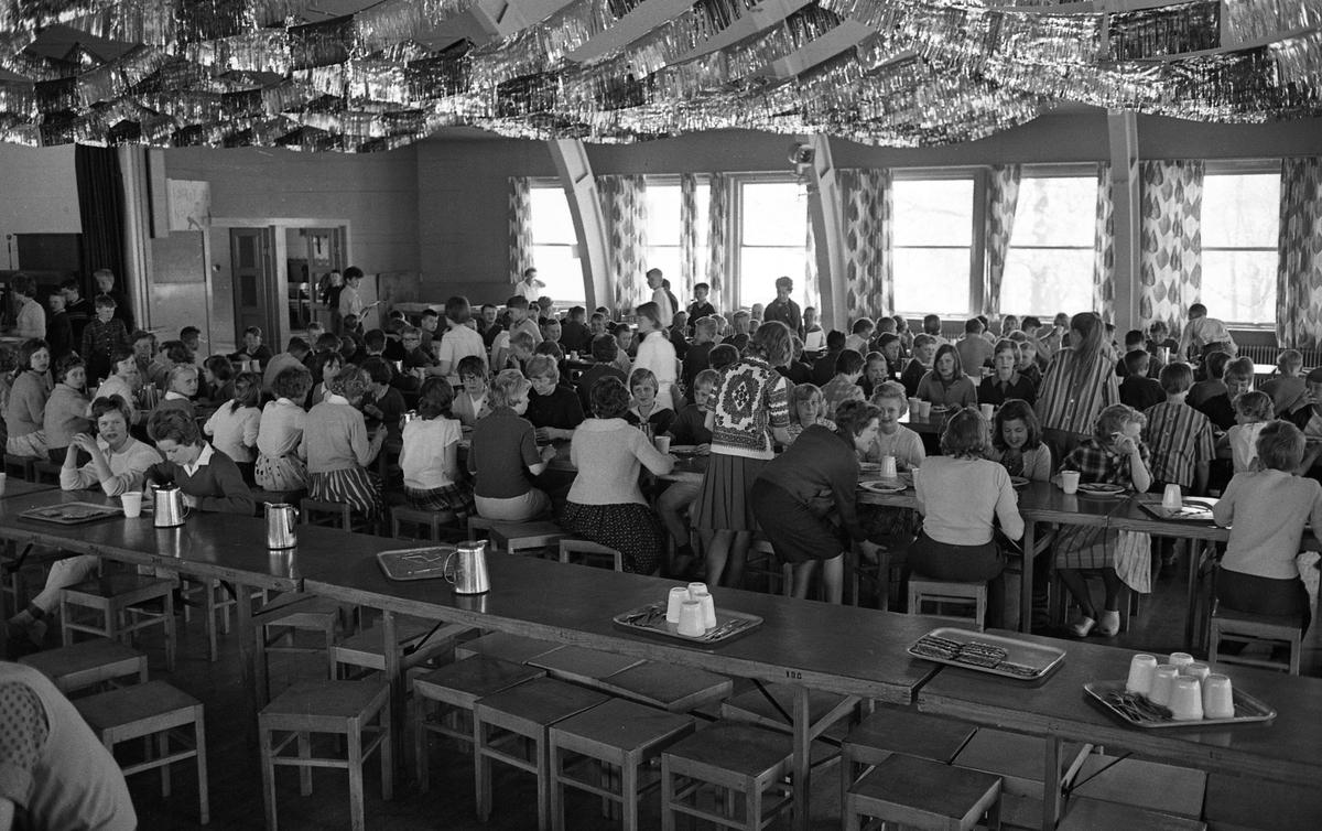 Matrast i skolan. Eleverna äter vid långbord i skolbespisningen. Maten kommer från AB Stig Dahlberg Storkök i Medåker. Brickor med färdigbredda, hårda smörgåsar. Rostfria kannor på borden. Bilden är troligen tagen i Köpings Folkets park, som fungerade som skolbespisning under en period.