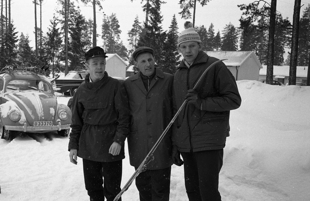 Skidtävlingen AT-loppet. Tre män i ytterkläder. En av dem, Hans Ekberg, håller i en längdskida. I bakgrunden syns bebyggelse och en folkvagn. (AT kan betyda Arboga Tidning)
