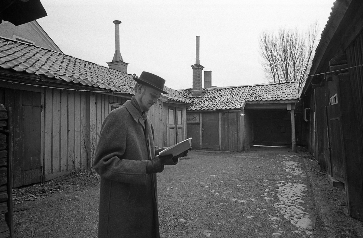 Kvarteret Tullnären, mellan Storgatan - Trädgårdsgatan och Herrgårdsgatan - Paradisgränd. Exteriör mot innegården. En man, klädd i rock och hatt, läser i några papper.