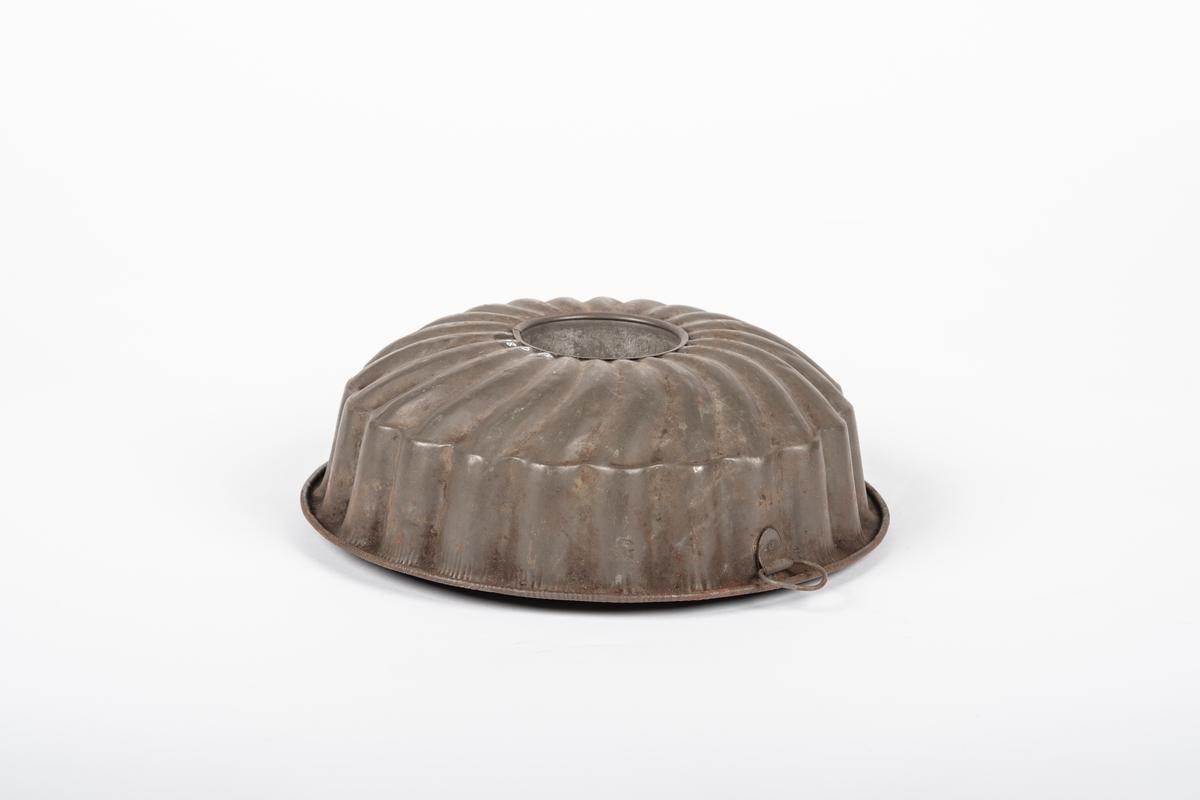Rund form med sylinderformet hull i midten, og med viftemønster i bunnen. Den har en liten hank.