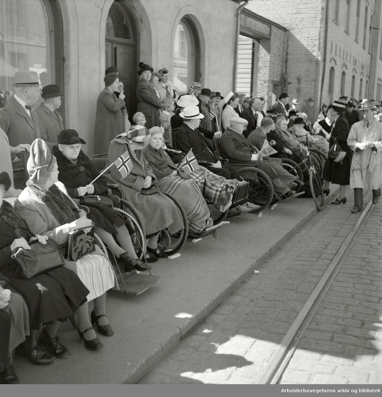 "Pasienter ved Prinds Christian Augusts Minde i Storgata 36, 17. mai 1951. ""Hele fortauet foran ""Prindsen"" var ""fredet"", og der satt de gamle og invalidene i sine vogner, strålende glade over det gode været. Bestyrer Bjelke, oversøster Agnes Magnussen og postsøster Helene Andersen sto bak og passet på at alle hadde det bra."" Pledd. Rullestoler."