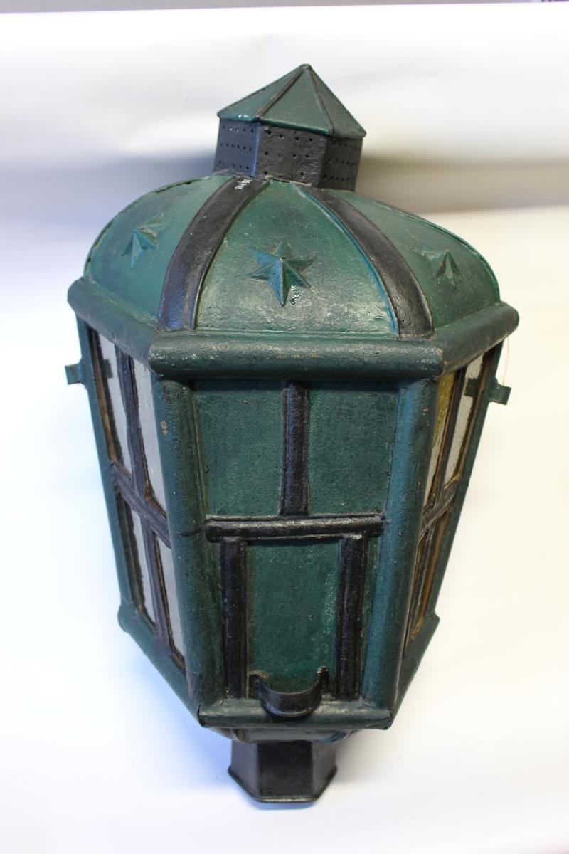 Akterlanterne av jern med 2 lysholdere, fra siste halvdel av  1700-tallet benyttet ombord på seilskip. Liten luke på bakside som kan tas opp for innsettelse av lys.
