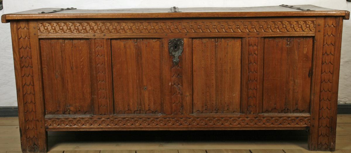 Eik, smijern. Flatt lokk, front og kortsider dannet av rammer og fyllinger. Ved hjørnene er langsidenes stående rammebord forlenget ned til føtter. Rammene er utskåret med renessanseliknende blad-, rosett- og kjedeborder, fyllingene med gotisklignende foldeverk. 3 smijernsbeslag på lokket, smijerns nøkkelskilt.