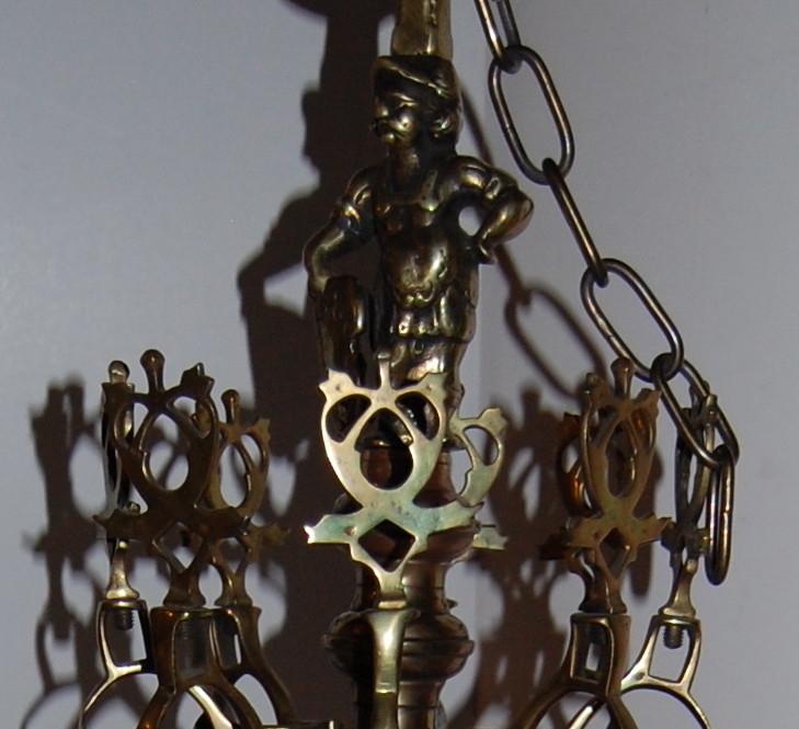 Lysekrone med balusterformet stamme. 8 lysarmer festet til nedre del av stammen. Profilert kule nederst på stammen. Mannsfigur på toppstykket.   1 defekt lysarm (brukket).