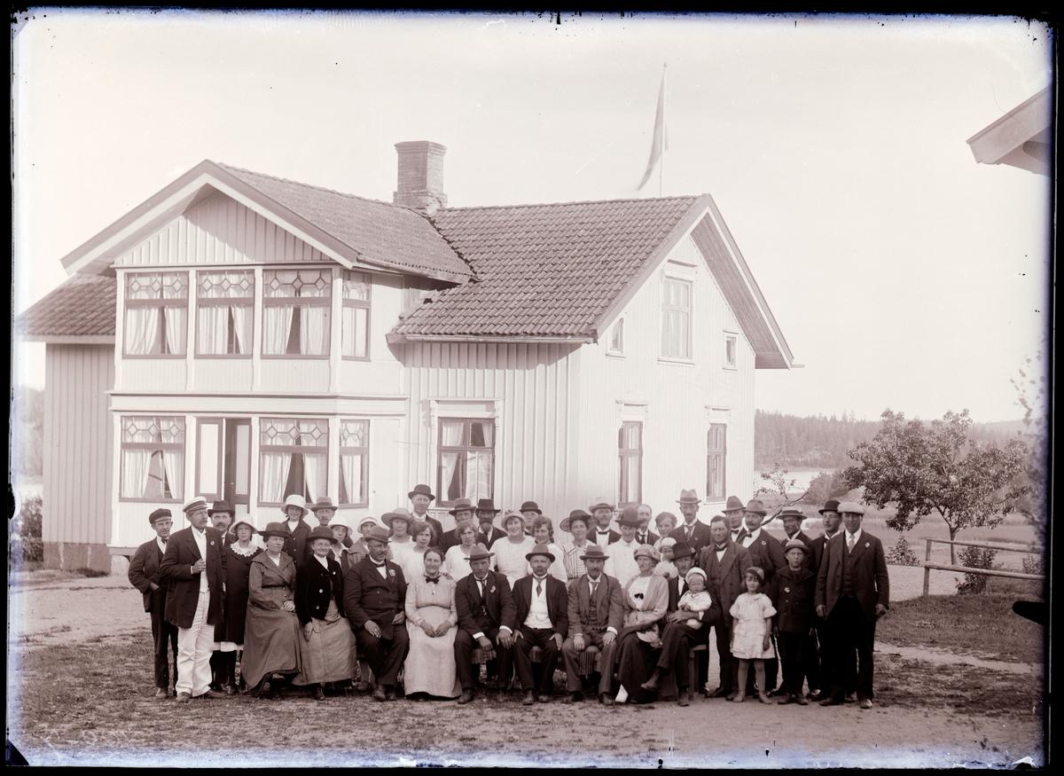 """Enligt noteringar: """"19 juli 1921. Frisinnade föreningen på sommarmöte hos Anders Pettersson på Elseröd. Färden till mötet företogs delvis med roddbåt från Kaserna i Munkedal. Några av personerna identifierade: Rad 1: nr. 6 Anders Pettersson, Elseröd (i vit väst). Rad 2: Sören Grundberg (ung man i svart skärmmössa). nr. 2 från vänster i vit skärmmössa troligen stationsmästare A.H. Svahn. Längst till höger Axel Sohlberg (klädd i keps) Bakersta raden: nr. 8 skogvaktare Albert Eriksson (hatt och mustasch), Melker Hansson.""""  Kvinnan med randig klänning och svart hatt kan vara Karin Elmér."""