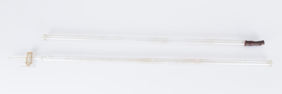 To avlange glassrør.1. Åpne - lukkemekanisme.2. m/gummi og en glasskule. Beholder i tre.