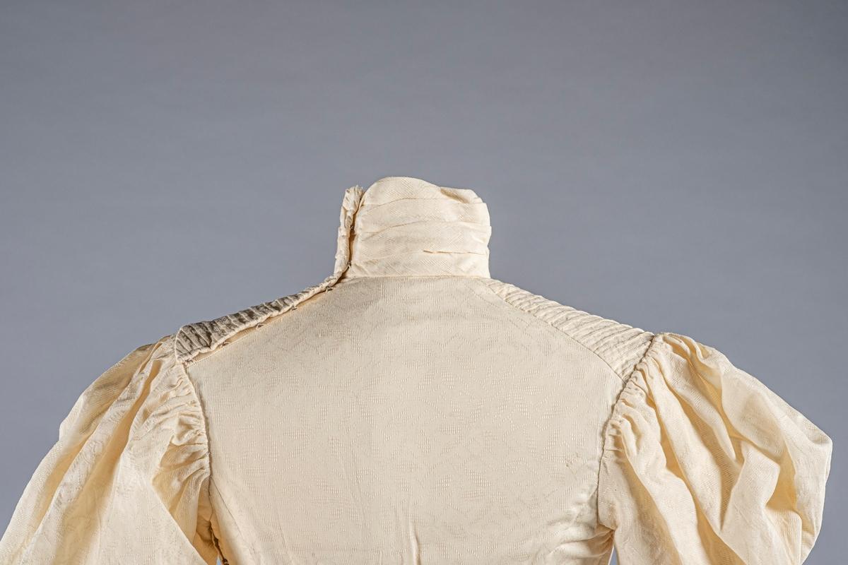 Kjole bestående av kjoleliv og skjørt. Stoffet på drakten har mønster og er kremfarget. Drakten er foret med lin (?).   Kjolelivet har puffermer og høy hals. På framsiden er det sydd loddrette brett/ribber. På baksiden er det en metallhekte. Det er metallspiler på innsiden. Det er en liten brystlomme på den indre klaffen. Kjolelivet lukkes først på innsiden og deretter med en ytre klaff på venstre side. Den lukkes med metallhektere. På den ytre klaffen er det et bånd ved nedre kant.  Skjørtet med slep. Den lukkes med metallhekter på venstre side. På innsiden av linningen i midjen er det en hemp bak for hekting av kjoleliv.