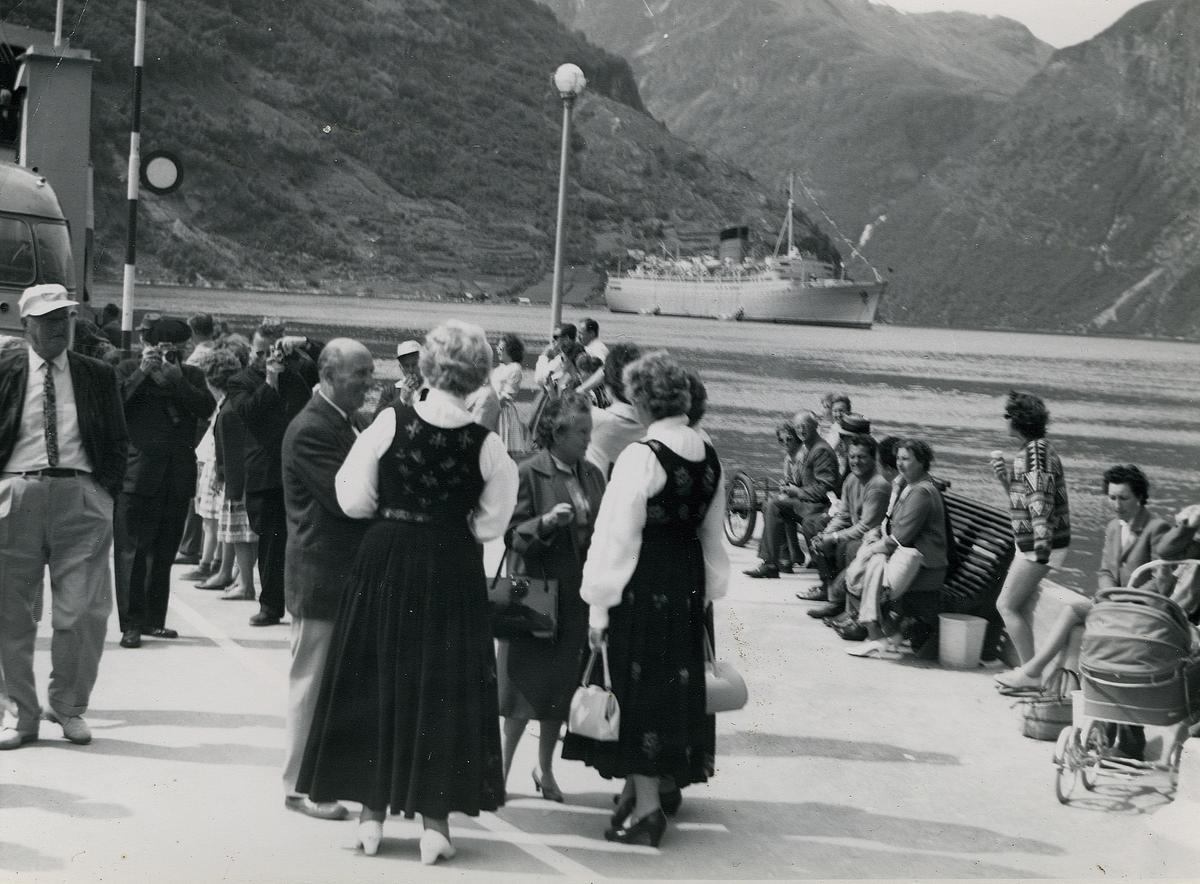 """Motiv av en folkemengde på fergekaia i Geiranger. På fjorden ligger et større cruiseskip RMS """"Caronia"""" fra selskapet Cunard Lines. I forgrunnen står to kvinner i bunad."""