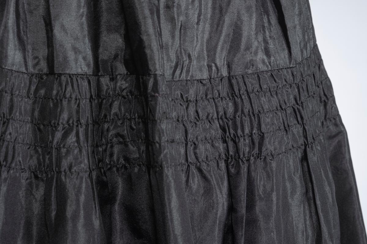 Skjørt i svart silke. Skjørtet har strikk i livet. Austmannarenning i overgangen mellom linning og skjørt. 15 cm. fra linningen et felt med rynkesøm, 4 sømmer i alt. Nederst er det montert sirkler og bånd (som danner et mønster) løst fra kant på skjørtet til falden, dette skaper en slags gitter.