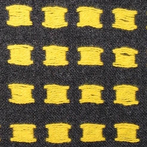 Vävprov till beklädnadstyg vävt i tuskaft med inslagsflottering i tvåtrådigt ullgarn, filtgarn. Varpen och botteninslaget är natursvart medan flotteringen är starkt gult. Inslagsflotteringarna bildar stora gula prickar på rätsidan. På baksidan blir det lite längre flotteringar. Vävprovet har beretts genom lätt valkning och pressning. Vävprovet har en 50mm maskinfåll i vardera kortsidan. I den ena sidan har den fållats upp ytterligare en gång med en 65mm bred handfåll.   Vävprovet med modellnamn Dått är formgivet av Ann-Mari Nilsson och tillverkat av Länshemslöjden Skaraborg. Det finns ett vävprov monterat i aluminiumram, se inv.nr. 0041:12, som finns med på sidan 76-79 i vävboken Väv tyger till kläder av Ann-Mari Nilsson i samarbete med Länshemslöjden Skaraborg från 1989, ICA Bokförlag. Tyget är enligt boken lämpligt att använda till jacka eller kappa. i boken finns det ytterligare två färgställningar: blå och röd. Se även inv.nr 0041-0096 ur samma bok.