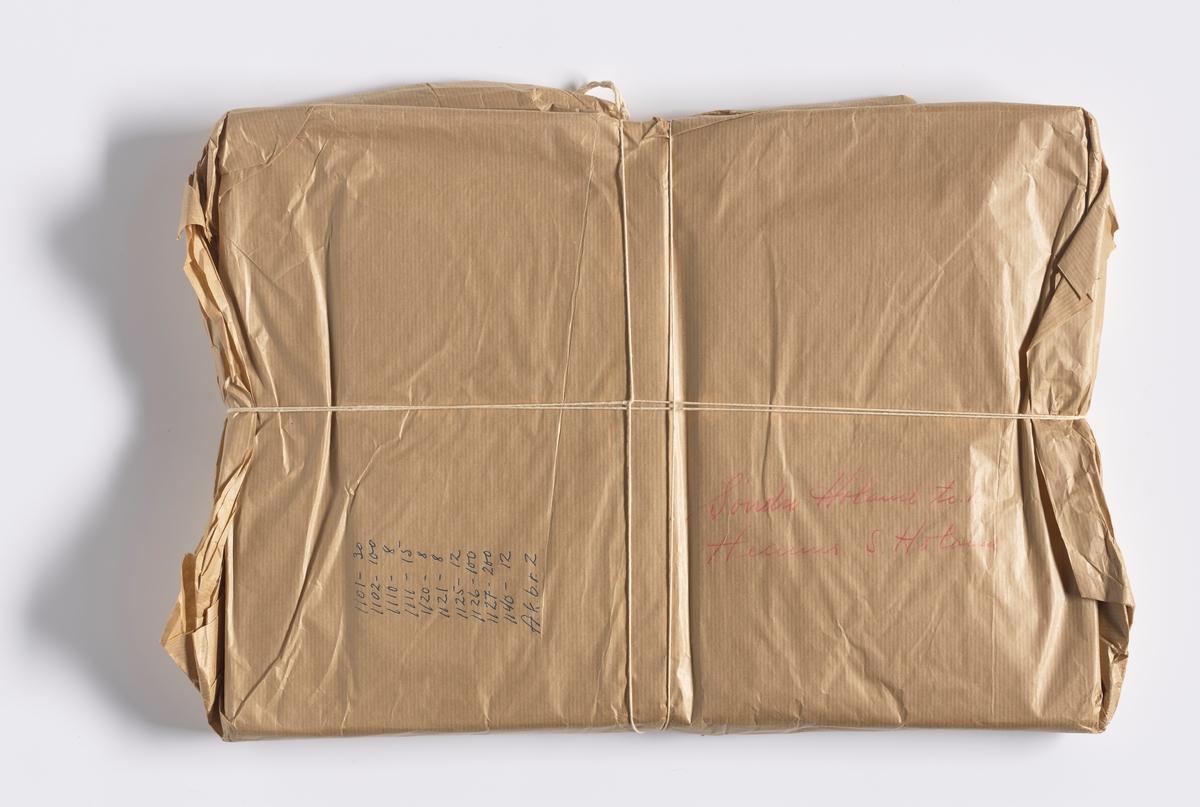 """Pakke med dokumenter innpakket i gråpapir. Rundt pakken er det knytt hyssing. På pakken er det skrevet i rød håndskrift: Søndre Høland (tre uleselige ord) S. Høland. Med blå penn er det skrevet """"1101 - 30, 1102 - 100, 1110 - 8, 1111 - 15, 1120 - 8, 1121 - 8, 1125 - 12, 1126 - 100, 1127 - 200, 1140 - 12, A. k. b. r. 2"""".  NAV-samlingen er en gruppe av gjenstander som har vært anvendt på sosialkontoret (Aetat - NAV) i Skedsmo kommune."""