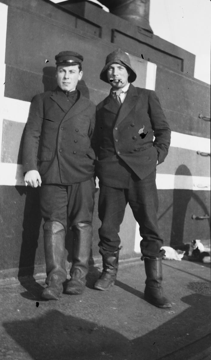Brødrene Waage foran norsk flagg (Nøytralitetsflagg) på dekk ombord på D/S STORFOND. Til venstre styrmann Ferdinand Waage og bestmann Georg Waage. Tre katter i bakgrunnen.