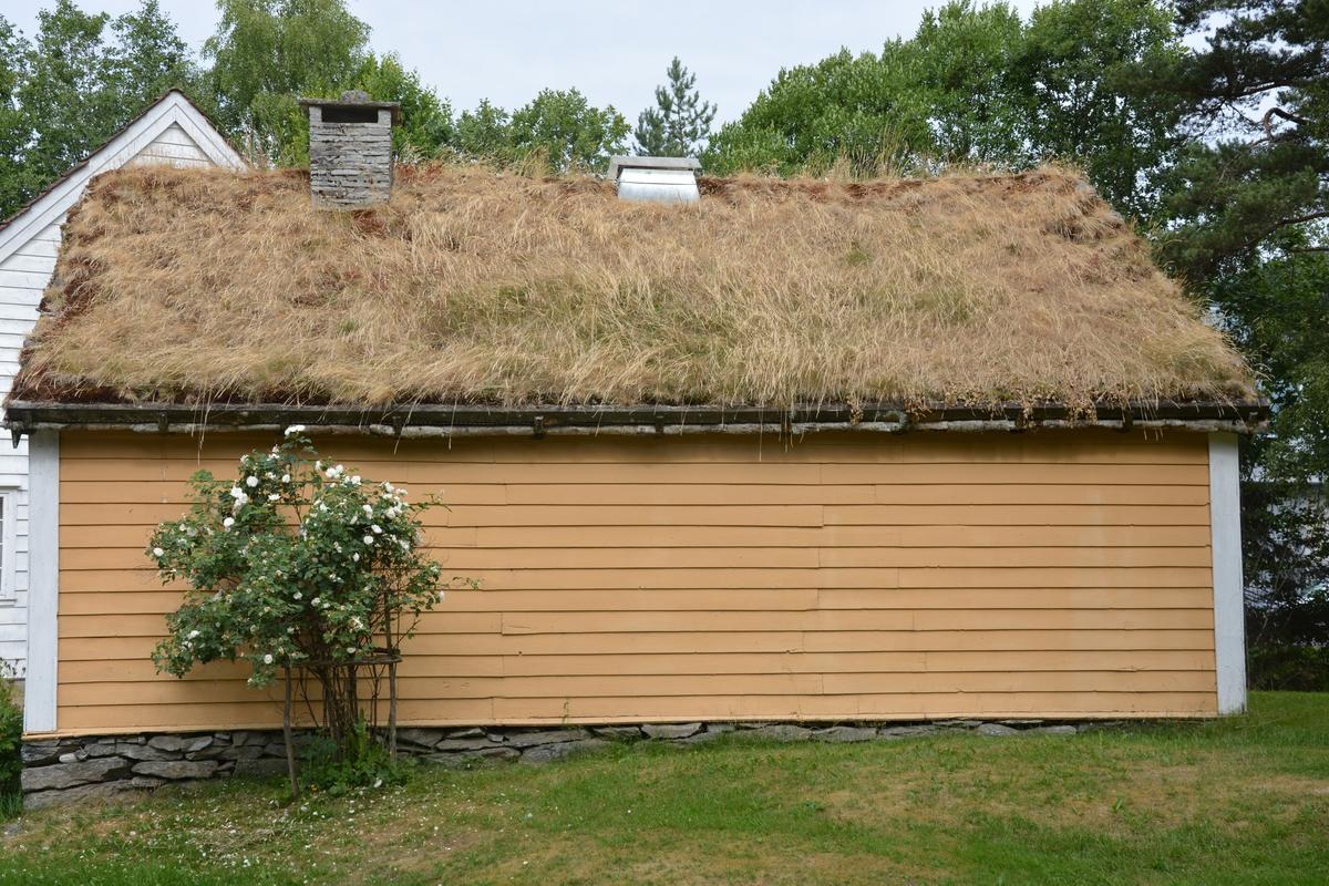 "Tømra bygning med treromsplan: forstove/""Døra"", skulestova og kammes. Jarnomn. Liggande panel. Torvtak."