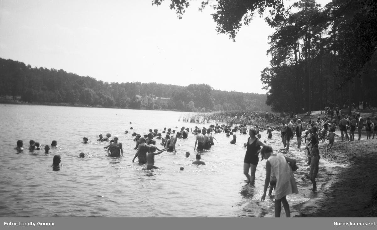 Motiv: Utlandet, Bad v. Berlin 147 - 156 ; Vy över en badstrand med människor som badar.
