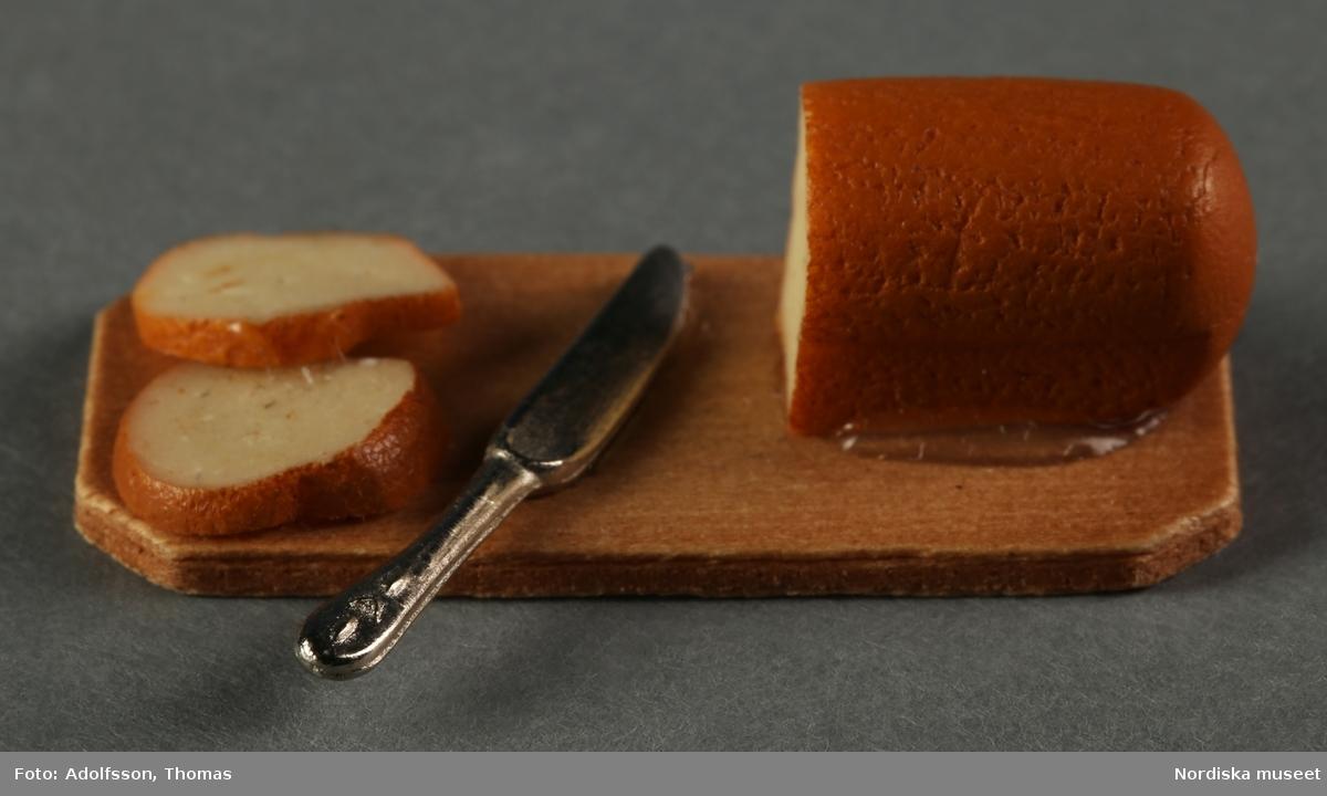 11 st matattrapper av blandade material, varav en a) gurka och b) ett bröd av plast eller konstmassa, c-d) 2 st skärbrädor av trä med bröd och ost, e-f) 2 trätallrikar med tårta och tårtbit, g) en vit kartong med bröd (tillverkade av vita bönor), h-j) 3 st tallrikar med  kött, frukt och grönsaker, stekta ägg och spenat, k) ett gipsfat med fisk och grönsaker. Hör till dockskåpsinredningen i matkällaren i dockskåp NM.0331721+.