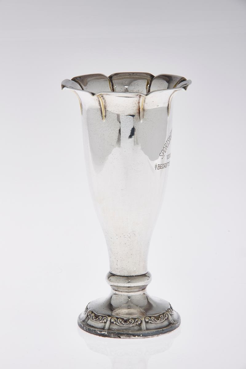 Traktformet pokal med form som en blomstervase i sølv(plett?). Åpningen øverst er formet som åttebladet blomst.  Åtte felter med akantusmønster nederst på stetten. Inskripsjoner.