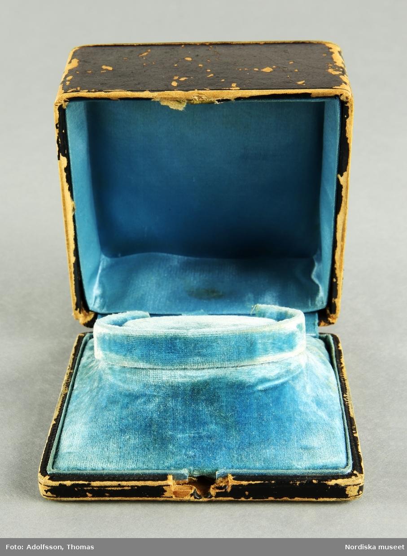 """A) Armring i något oval form, 18 k guld. Dekoration, längsmed armringen, av  genombruten filigrandekor samt litet bandornament i guld med  5 st små, gråvita, satta äkta pärlor. Armbandet är stelt och öpnas/slutes medelst """"klick""""-lås. Säkerhetskedja vid låset. Tillverkad 1888 av  Gustaf Dahlgren & Compani, Malmö. Försedd med kattfot.  B) Etuie för armband. Hölje i mörkbrunfärgad kartong med tunn gulddekor utmed lockets övre kanter. Etuiet på insidan klätt med ljusblå sammet och siden. En löstagbar bottenplatta klädd i ljusblå sammet med en upphöjning för fästandet av armbandet (också den klädd i ljusblå sammet).  /Cecilia Wallquist 2019-03-29"""
