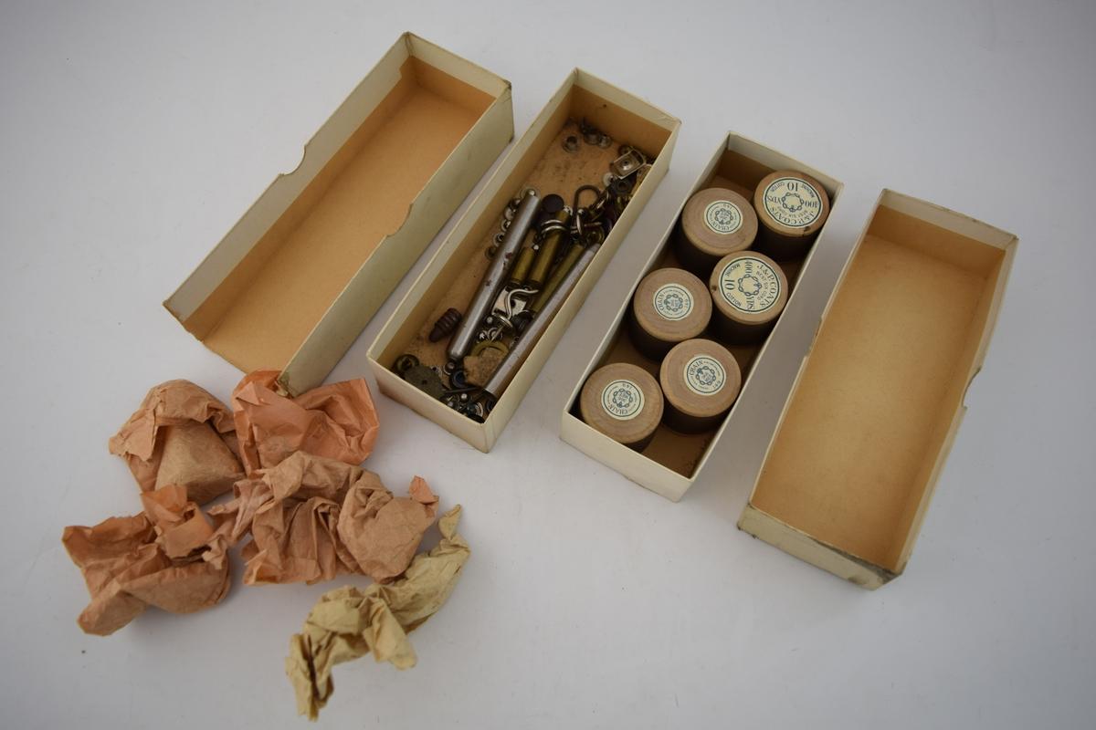To stk. papiresker med bunn og lokk. Den ene inneholder seks trådsneller med brun bomullstråd produsert i Stor Britannia. Den andre esken inneholder diverse små metalldeler som knapper, spenner og lignende, trolig deler som har vært brukt på sko tidligere. Ingen etiketter eller påskrifter på eskene.