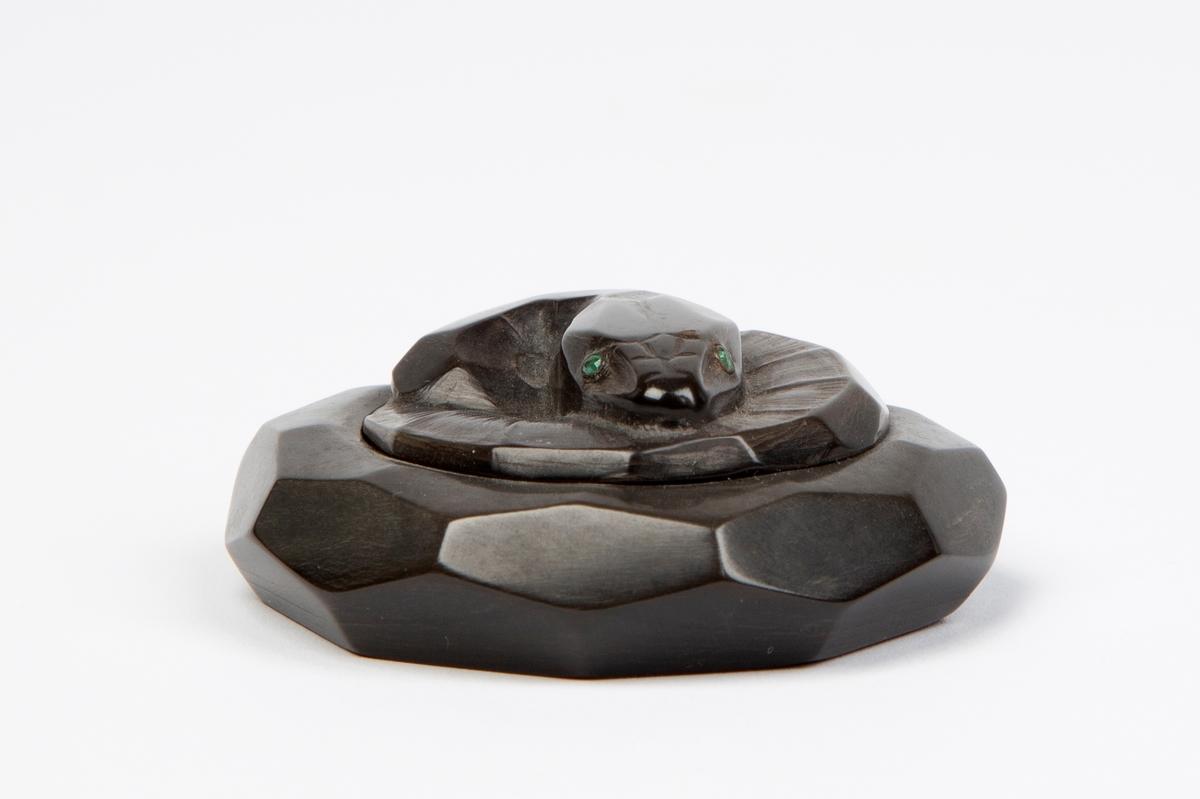 Puddereske i sortfarvet ben, utformet som en sammenkveilet slange med øyne av smaragder.