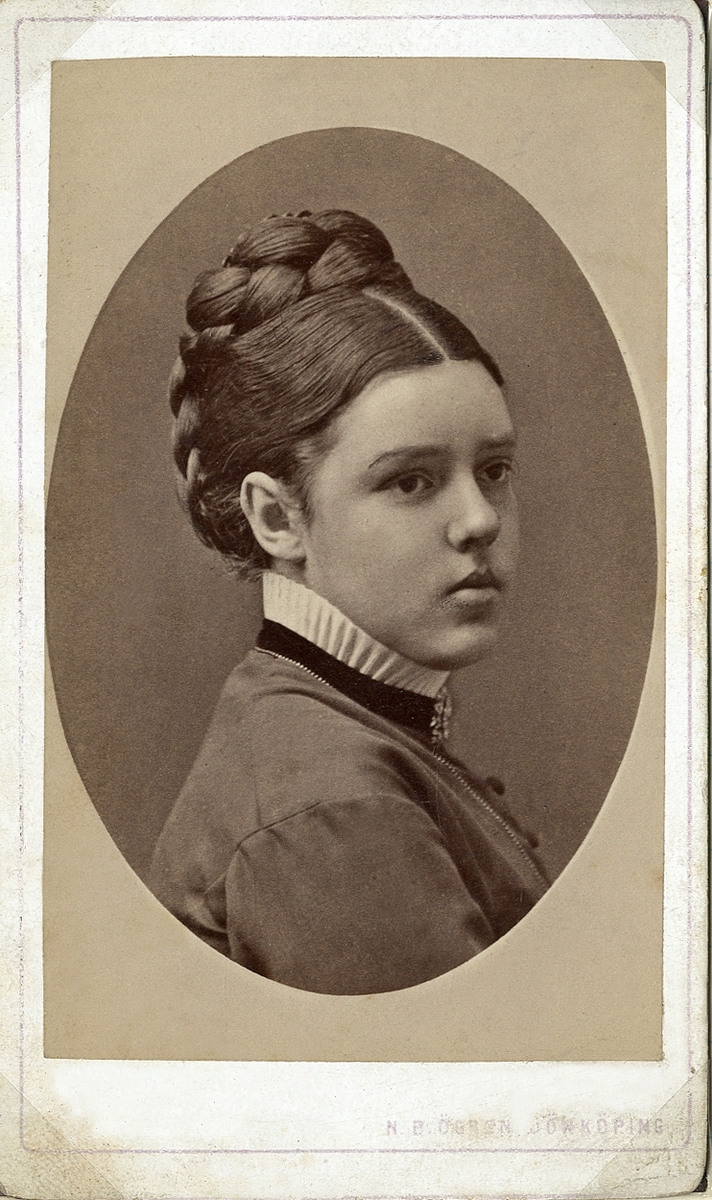 Porträttfoto av en kvinna i klänning med vit kråskrage.Vid kragens sammetsband skymtar en brosch.  Hög flätfrisyr. Bröstbild, halvprofil. Ateljéfoto.