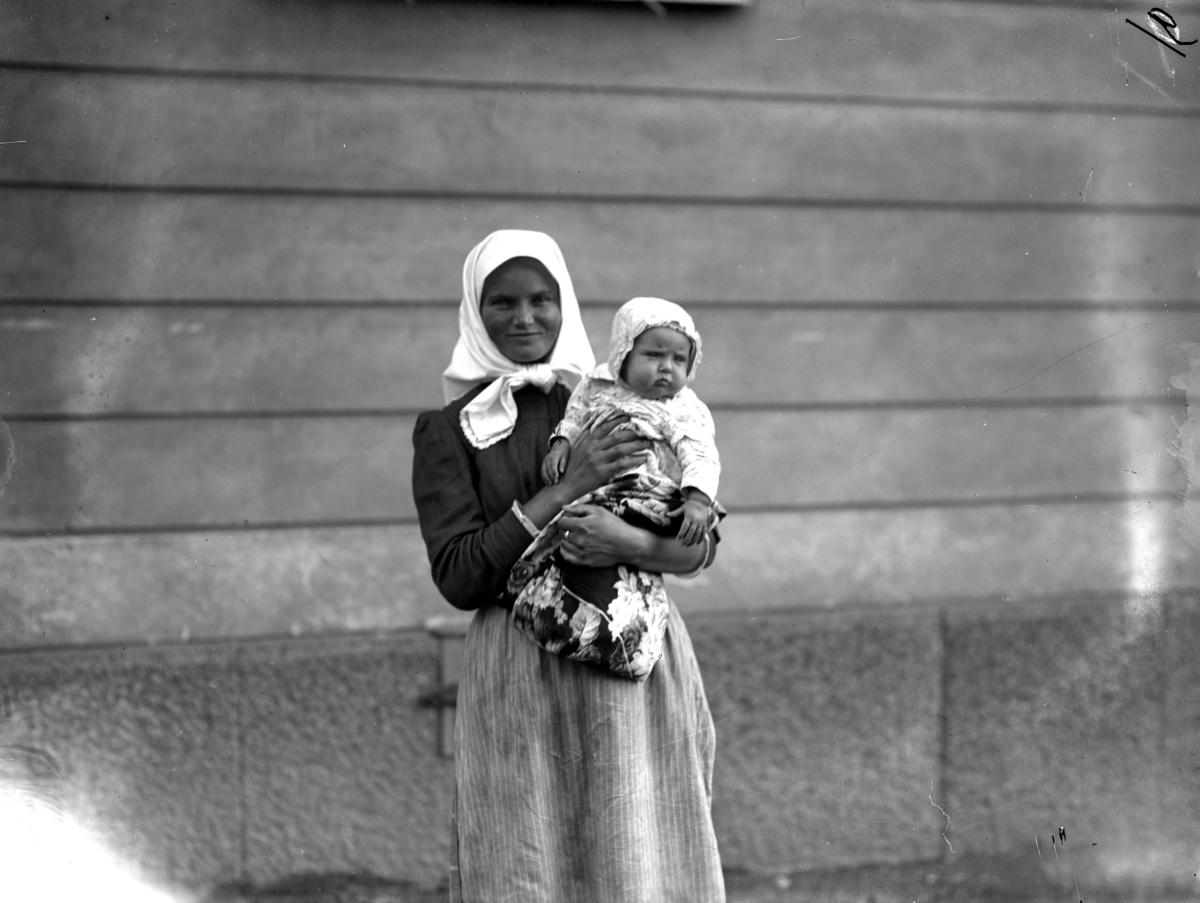 En kvinna med barn från svenskbyborna är fotograferad utanför kasernen på Ryhov i Jönköping 1929.
