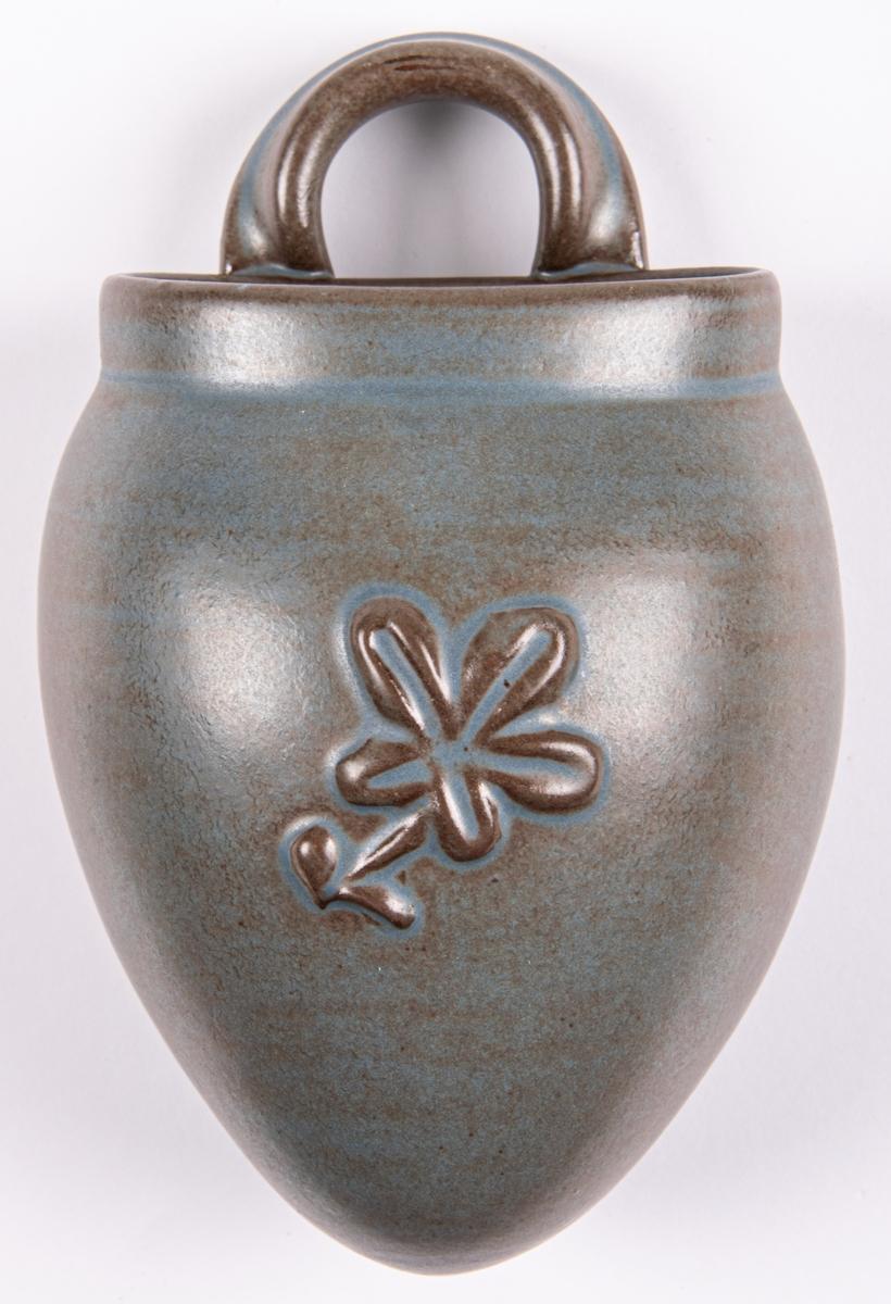Väggvas tillverkad vid Bobergs Fajansfabrik och formgiven av Eva Jancke-Björk, 1942-1948. Matt grön konstglasyr med bruna skiftningar. Artikelnummer 3333/33.