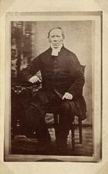 Foto av en medelålders man i prästrock och prästkrage. Han s