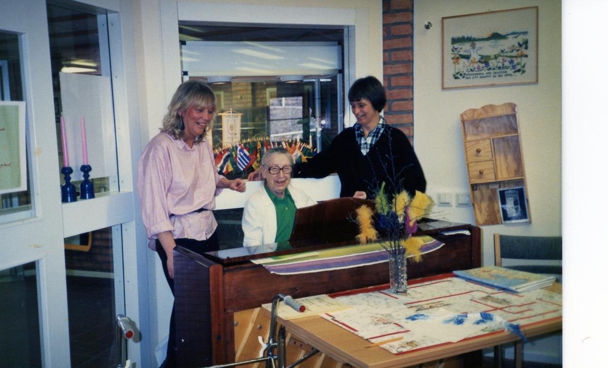 Musikunderhållning i Brattåsgårdens hobbylokal på Våmmedalsvägen 1980-tal. Från vänster ses vårdbiträde Susanne Olsen, vid pianot (tidigare pianolärare) Marianne Skarin (1906 - 1991) och vårdbiträde Anna-Lisa.