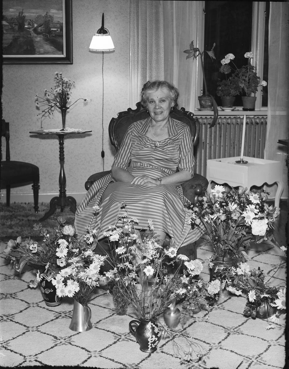 Kvinna i bostadsmiljö omgiven av blommor, Östhammar, Uppland