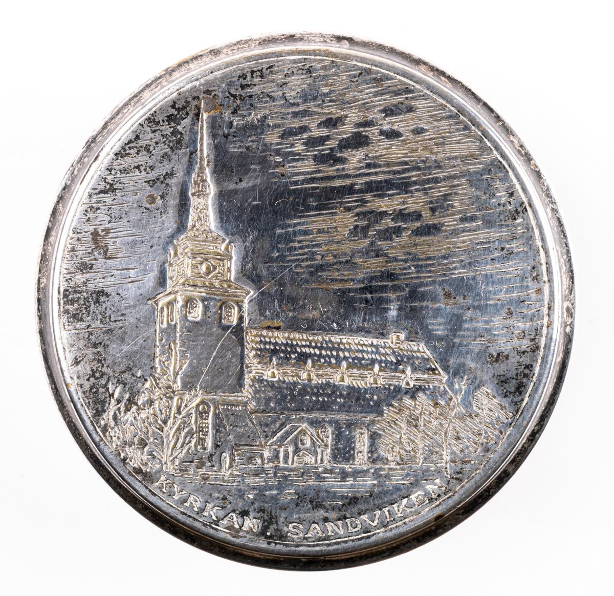 En liten försilvrad dosa med lock och tre runda kulfötter. På locket en pressad bild av Sandvikens kyrka samt texten KYRKAN SANDVIKEN.